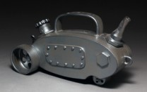 Teapot on wheels Description: Wheel-thrown and hand build stoneware. Fire to cone 6 in oxidation.Dimensions: H:5.00 x W:10.00 x D:5.00 Inches