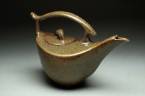 Teapot Description: High fired stoneware, wheel thrown and slab built, golden brown glaze Dimensions: H:7.50 x W:9.50 x D:0.00 Inches