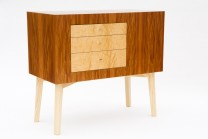 Description: This display table is veneered in ropey timborana.  The drawer faces are veneered in ash burl, the legs are solid ash.  The piece exemplifies Todd's design aesthetic; chunky and solid looking, with contrasting wood and playful asymmetry.Dimensions: H:34.00 x W:34.00 x D:18.00 Inches