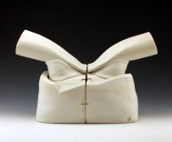Description: This is a sculptural stoneware split lidded vessel that is fired to cone 6 in an oxidation environment. It is thrown and slab built. A matte-finish white glaze is sprayed on.Dimensions: H:11.00 x W:10.00 x D:25.00 Inches